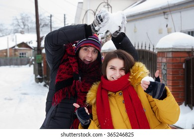 Young cheerful couple fooling around on the snow in the village