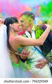 Young cheerful couple at Holi paint party