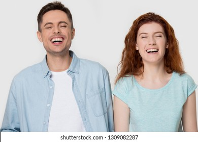 Young cheerful couple laughing at humorous hilarious silly funny comedy joke together, happy man and woman burst with laughter chuckling giggling having fun isolated on white grey blank background