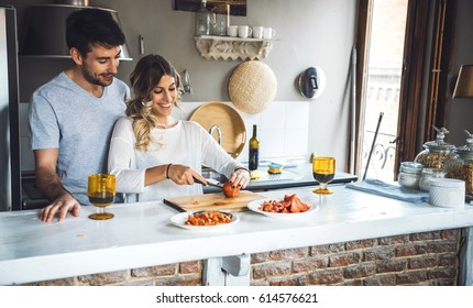 Young cheerful couple making dinner in modern kitchen.