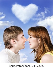 Young cheerful couple on sky background with heart