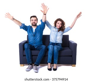 young cheerful couple sitting on sofa and watching football isolated on white background