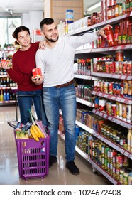 Young cheerful  couple standing near shelves with canned goods at store