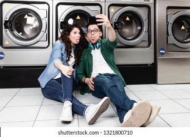 Young cheerful couple taking selfie photo at laundromat shop.