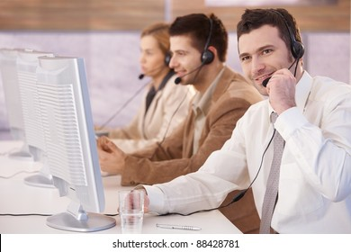 Young cheerful customer servicer working in call center, smiling.?