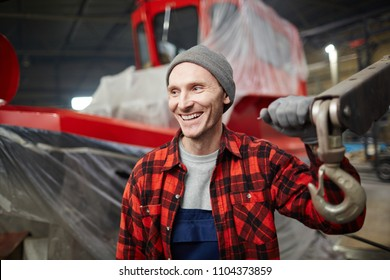 Young cheerful engineer of shipbuilding factory holding by part of industrial machine during work