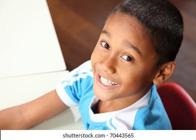 Young cheerful ethnic school boy in classroom