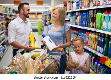 Young cheerful family shopping household goods in supermarket