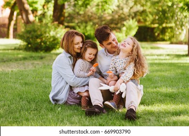 Young cheerful family sitting on grass enjoying vocation and keeping their children on knees. People sitting in summer park. Sunny day, outdoors