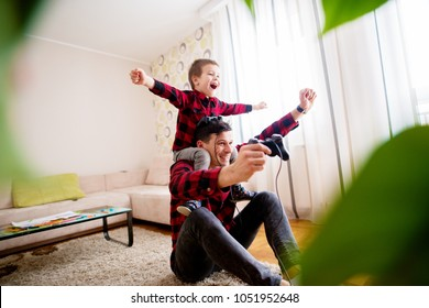 Young cheerful father celebrating victory on a console game with a happy son that is piggyback riding him in a bright living room.