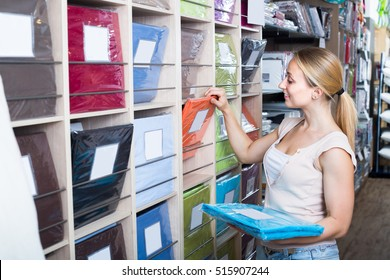 Young cheerful female choosing cotton bedding set in home textile store