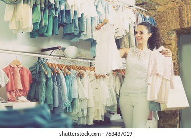 Young cheerful female customer choosing baby dress in kids apparel boutique