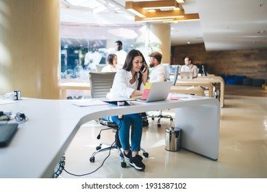 Young cheerful female employee in casual wear sitting at table and discussing work issues on smartphone while typing on laptop on background of team of colleagues