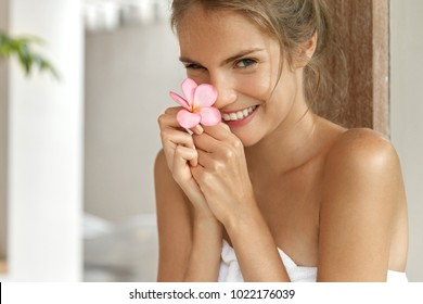 Young cheerful female with pleasant charming smile wrapped in towel, satisfied with new bath lotion, has soft fresh healthy skin after taking shower. Lovely young woman poses indoor in bathroom