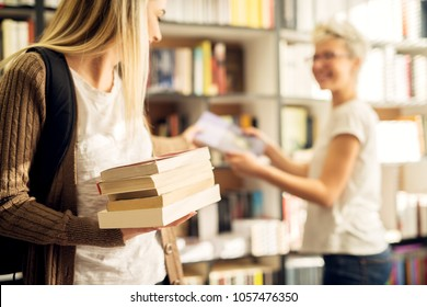 A young cheerful female student is taking the book from a female dedicated joyful librarian and stacking them in other hand.