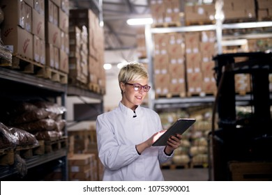 Young cheerful female worker is using her tablet in factory storage area.