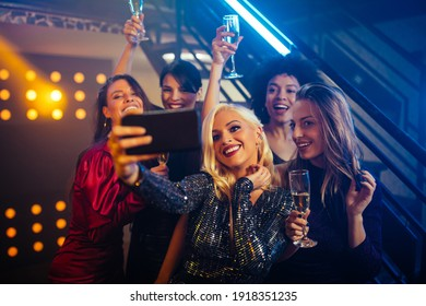 Young cheerful females taking a selfie together in a nightclub