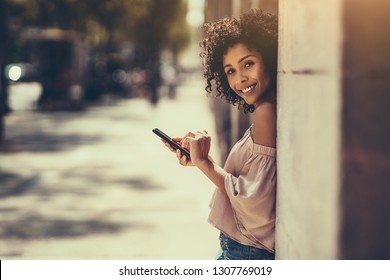 A young cheerful flirtatious curly-hair biracial female outdoors is leaning against the stone column or wall while typing a message using the smartphone, with a copy space place for an advert message