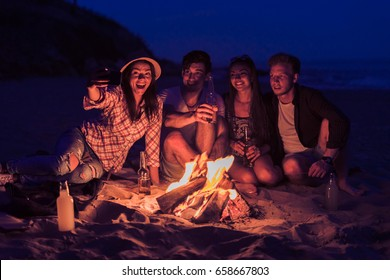 young and cheerful friends sitting on beach and take selfie near bonfire One man is drinking beer. Happy lifestyle