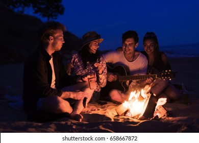 young and cheerful friends sitting on beach and fry sasuages or weenies in bonfire One man is playing guitar. Music on Wild beach. Happy couple relationships.
