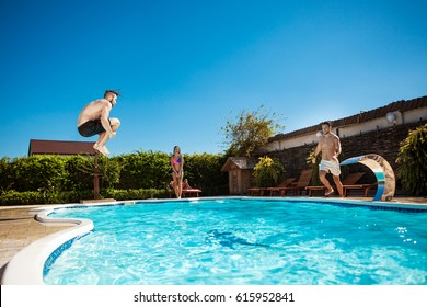 Young cheerful friends smiling, relaxing, jumping in swimming pool.