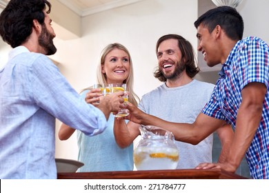 young cheerful friends toasting indoors at gathering