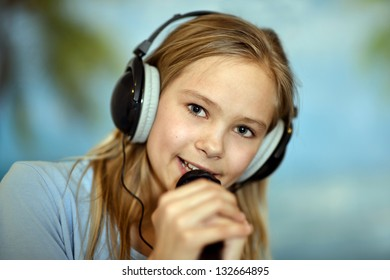 Young cheerful girl in the blue shirt singing a song