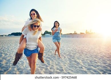 Young cheerful girl giving her friend piggyback ride while third girl laughing at them.