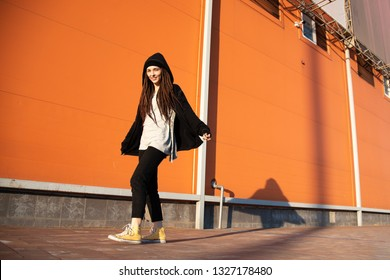 young cheerful girl with a hood and a black mantle against the background of an orange wall