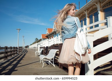 Young cheerful girl on the seashore. Young beautiful blonde on a walk, happy