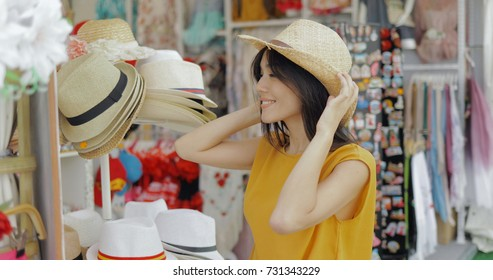 Young cheerful girl posing in shop of accessories trying on straw hat and looking at mirror while shopping in mall.