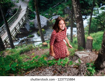 young cheerful girl in a red dress walks through the woods near the river and bridge
