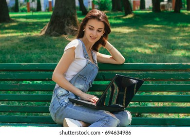 young cheerful girl sits on a bench and using a laptop at the park
