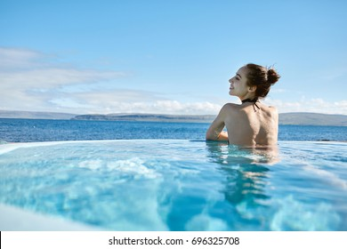Young cheerful girl swimming in water of pool looking away on background of sea, Iceland, West Fjords. back view