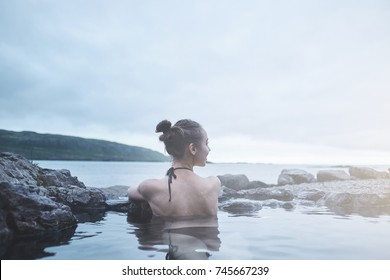 Young cheerful girl swimming in water of pool looking away on background of sea, Iceland, West Fjords. back view, Woman washing and covering her face with her hands
