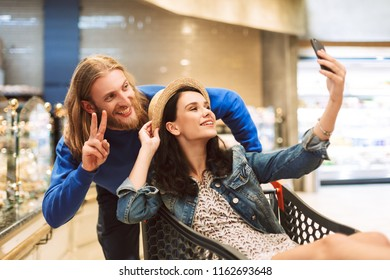 Young cheerful guy with pretty girl inside shopping trolley taking cute photos together on cellphone in modern supermarket