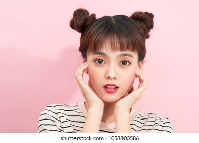 Young cheerful happy ginger girl with buns over pink background.