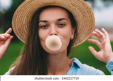 Young cheerful happy hipster woman in hat blowing bubble of chewing gum outdoor