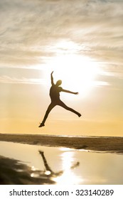 Young cheerful jumping girl silhouette in rays of sunlight at sunset on the beach. Vibrant outdoors vertical image.