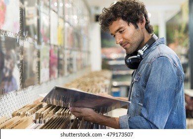 Young cheerful man browsing vinyl album in a record store