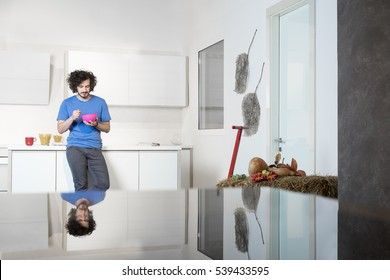 Young cheerful man eating cereal from a bowl in modern kitchen