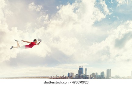 Young cheerful man flying high above city