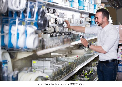 Young cheerful man standing next to showcase with electrical switches and plugs
