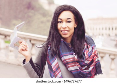 Young cheerful moroccan girl visiting Rome with city map in hand - Happy african female tourist traveling abroad in the spring - Concept of modern emancipated afro girl - Girl traveling in Rome