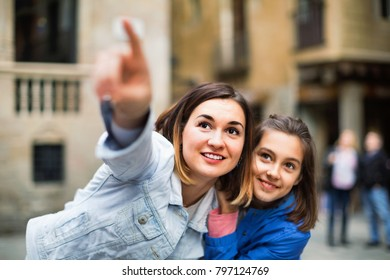 Young  cheerful  mother and daughter paying attention to sight during sightseeing tour