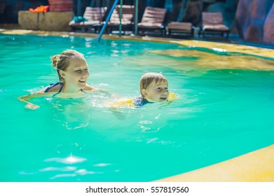 Young cheerful mother and son in a swimming pool. Holidays with family concept.