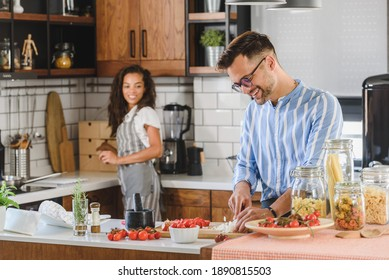 Young cheerful multiethnic couple preparing pasta together at their modern kitchen