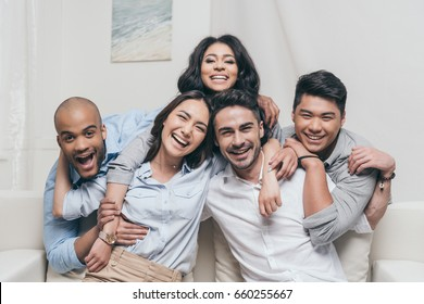 young cheerful multiethnic friends embracing while sitting on sofa at home
