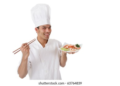 Young cheerful nepalese chef male holding shop-sticks and a plate with tasty oriental food. Studio shot. White background.