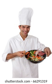 Young cheerful nepalese man chef shows oriental food in wok. Raw meat on side and fresh vegetables mix. Studio shot. White background.